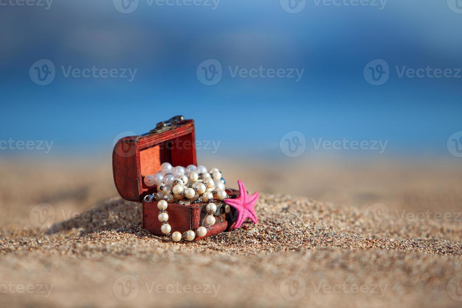 cofre decorativo con joyas y estrellas de mar en una playa foto