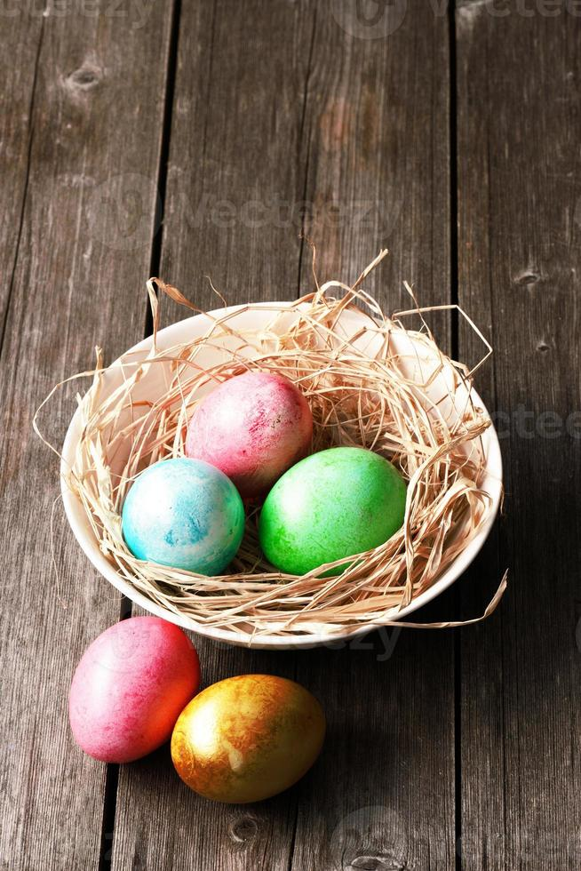 Colored easter eggs in nest photo