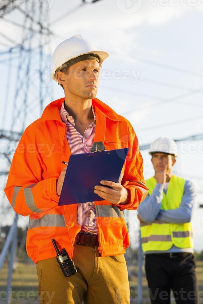 Arquitecto masculino con portapapeles trabajando en el sitio mientras el compañero de trabajo se encuentra foto