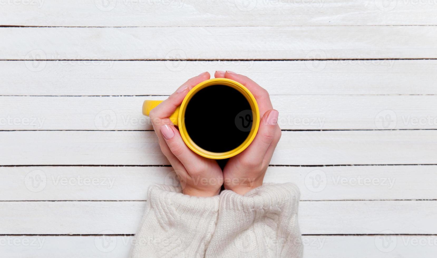 manos femeninas que sostienen la taza de café en la mesa de madera. foto