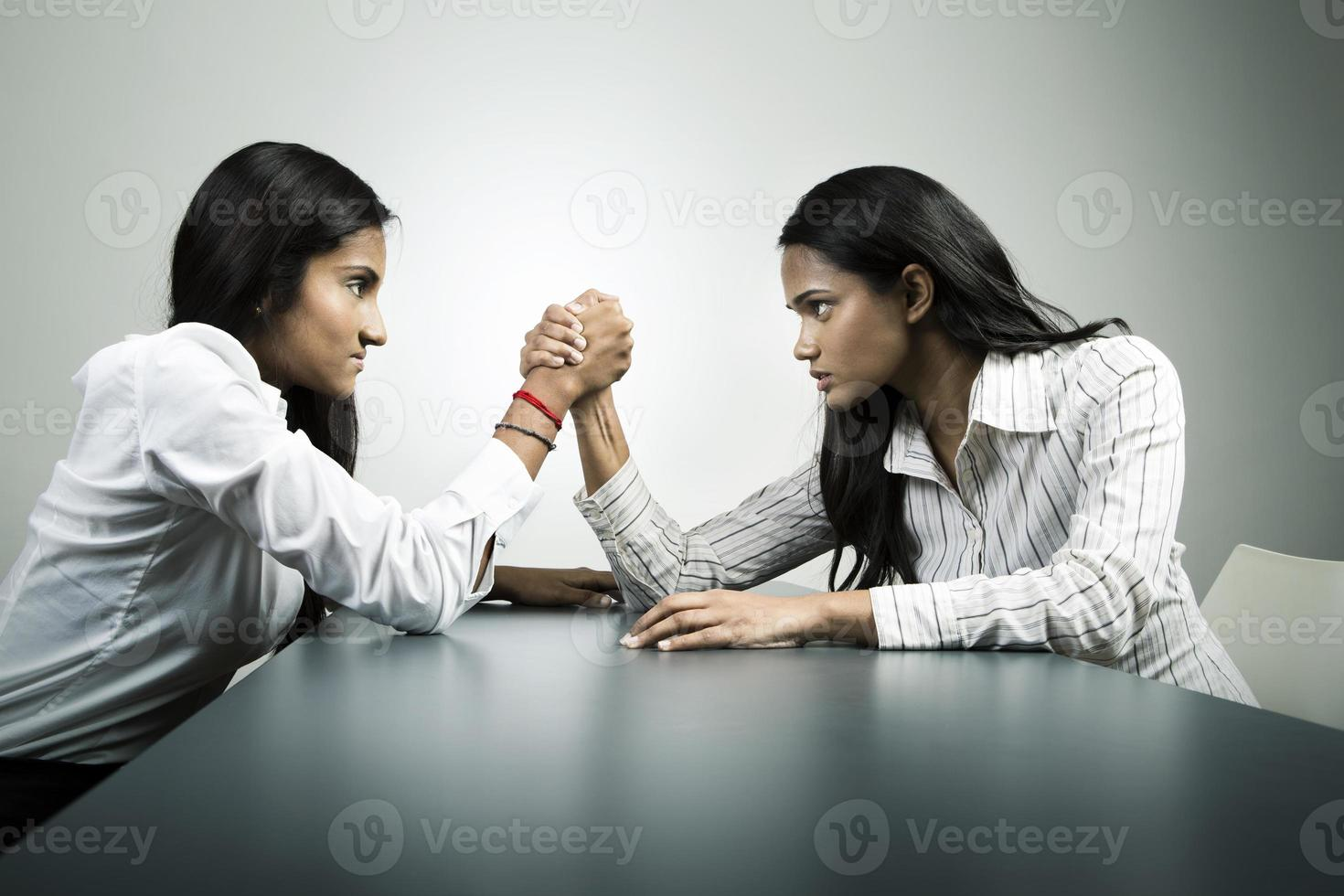 Business co-worker's arm wrestling for control. photo