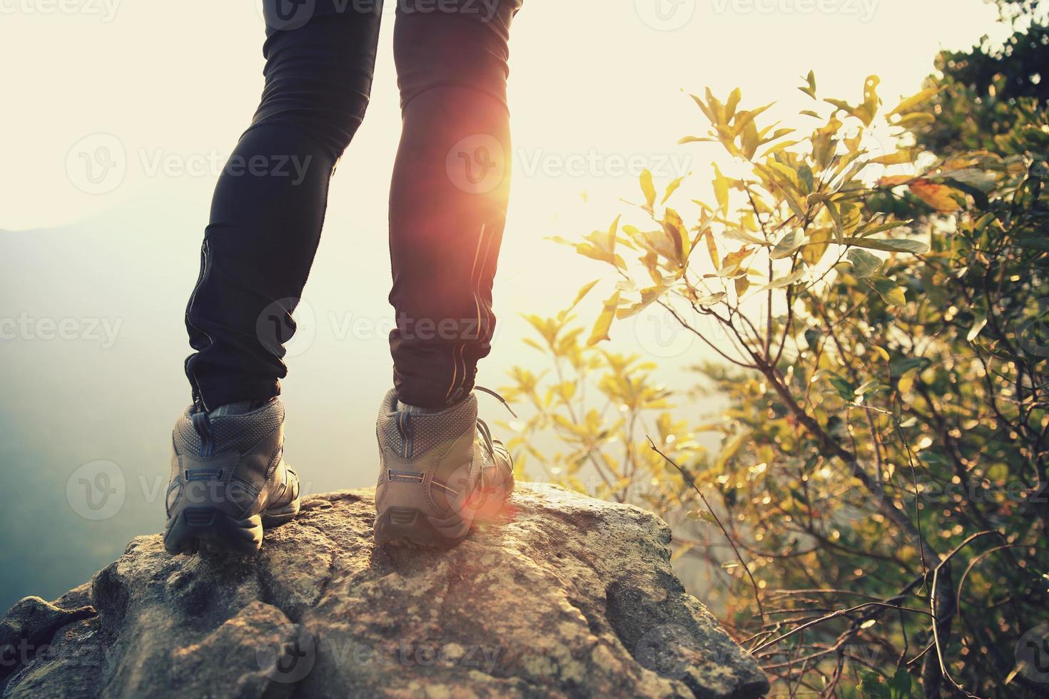 joven excursionista de pie en el pico de la montaña del amanecer foto