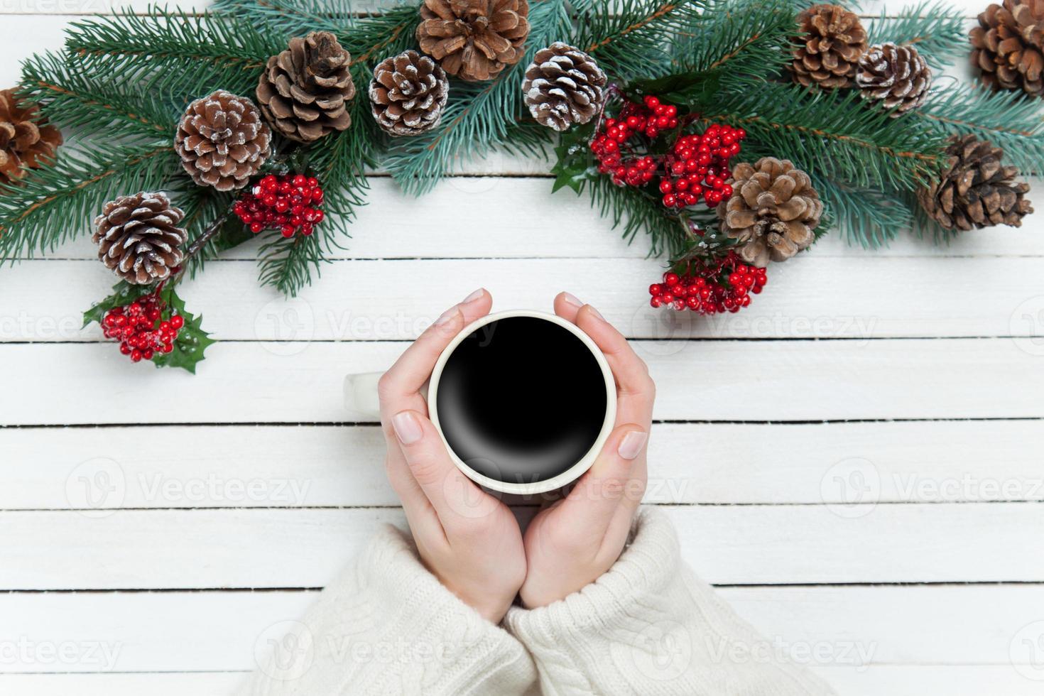 niña sosteniendo una taza de café cerca de ramas de pino foto
