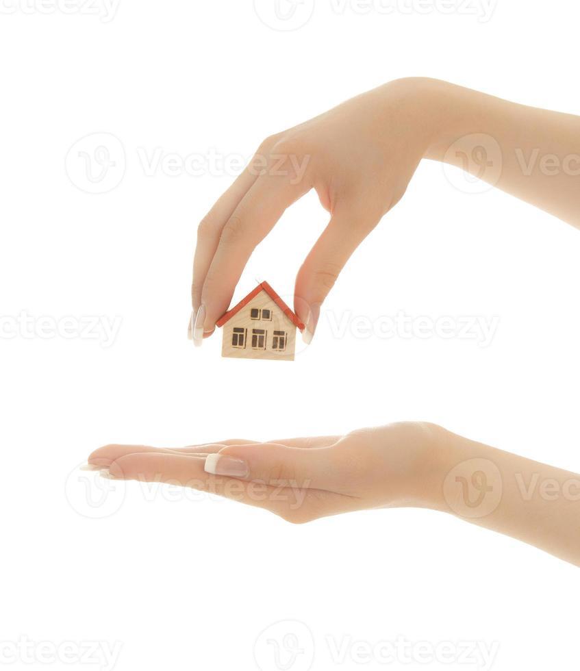 manos de mujer sosteniendo una casa de juguete aislada foto