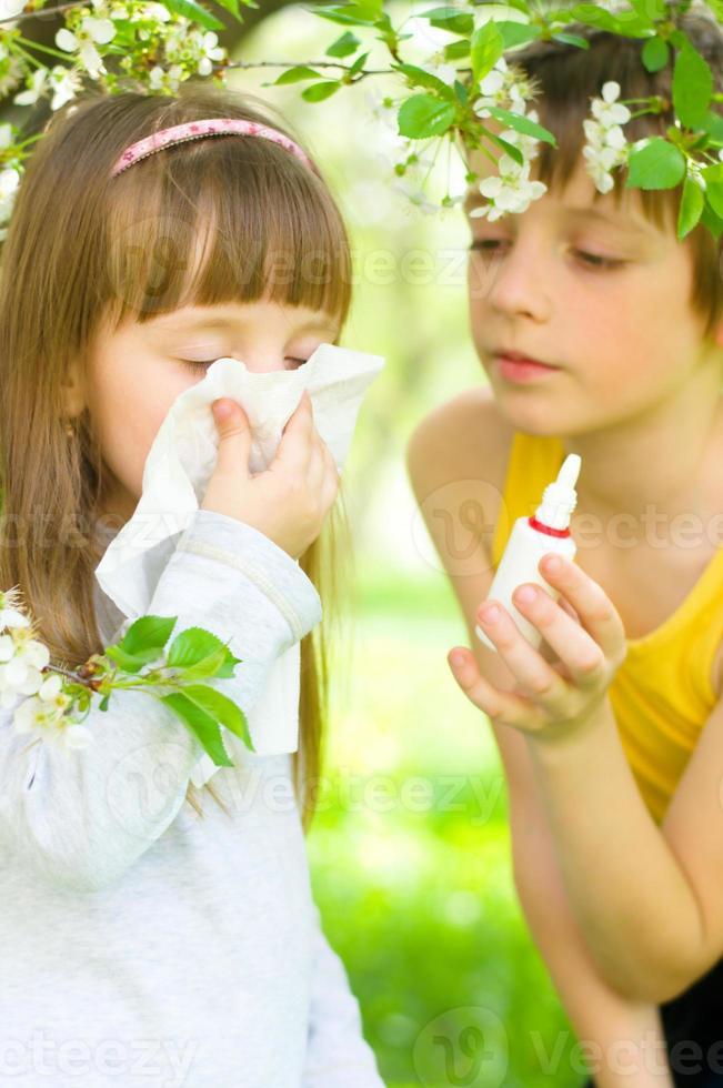 niña se sopla la nariz al aire libre foto
