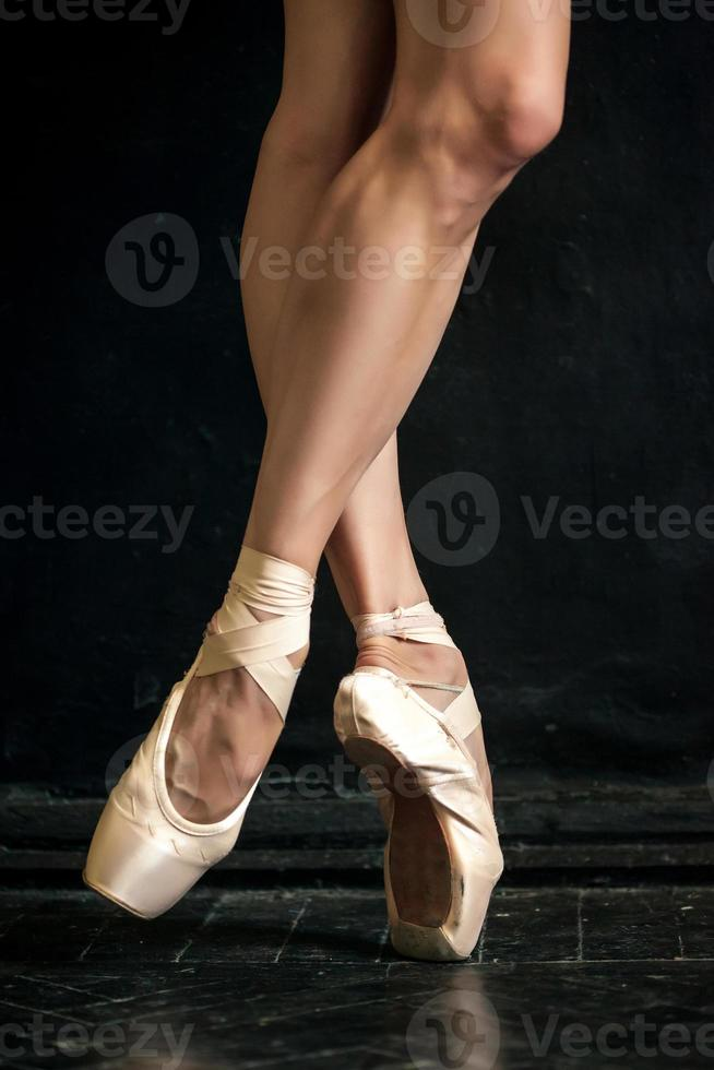 Close-up ballerina's legs in pointes on the black photo