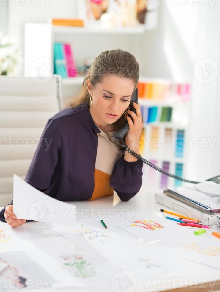 diseñador de moda en la oficina hablando por teléfono foto