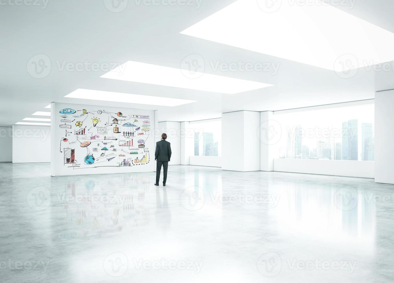 Young businessman standing in bright office photo