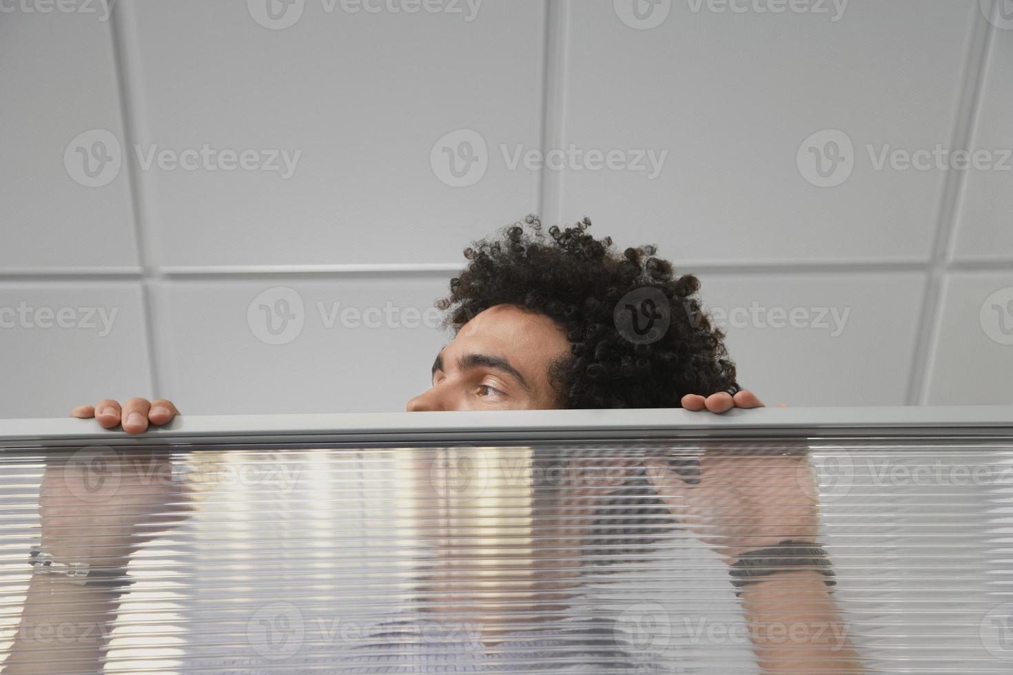 oficinista mirando por encima de la pared del cubículo foto