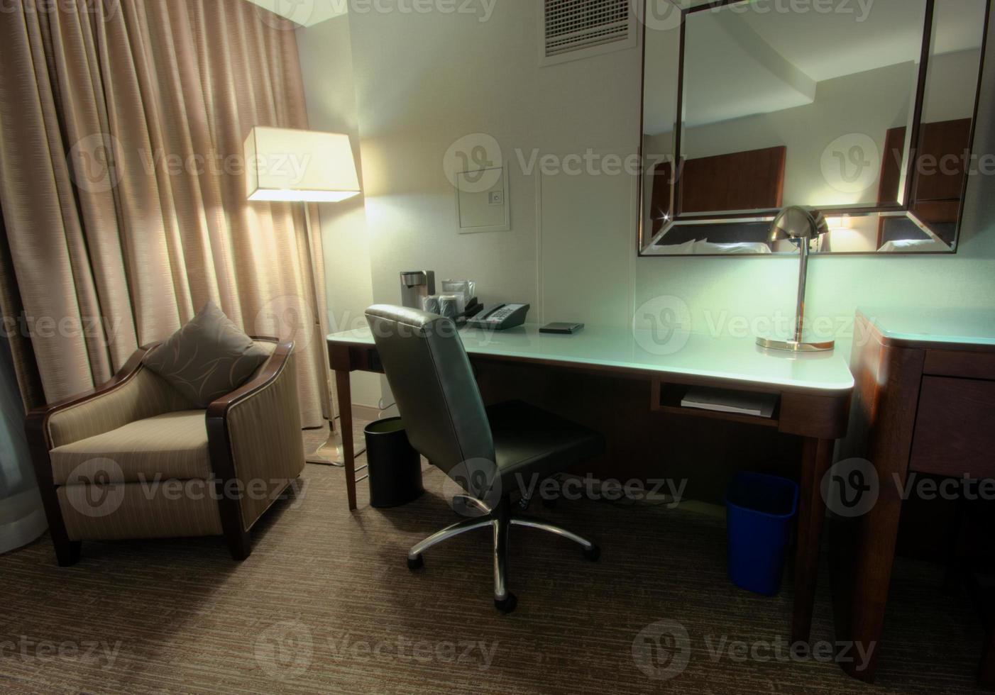 sala de estudio con escritorio, sillón, lámpara y espejo foto