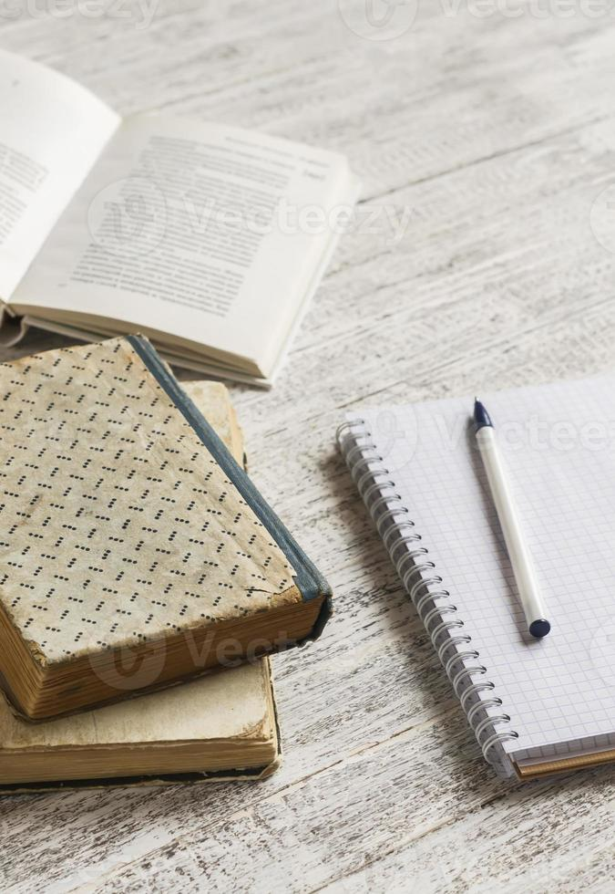 stack of books, notebook  on white wooden table. photo