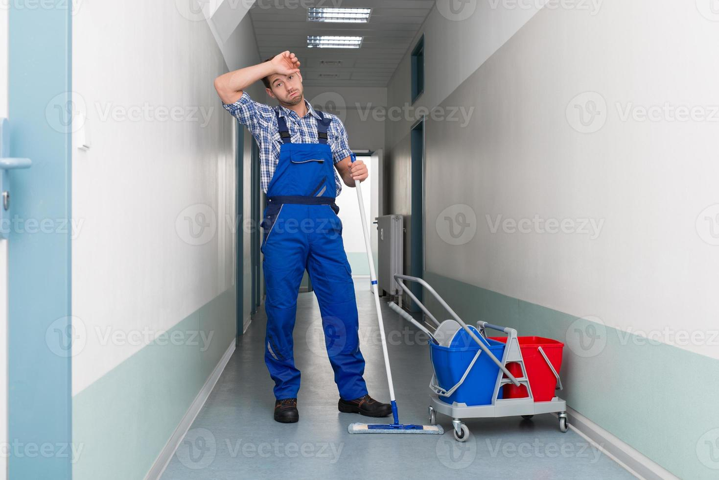 Tired Male Worker Cleaning Office Corridor photo