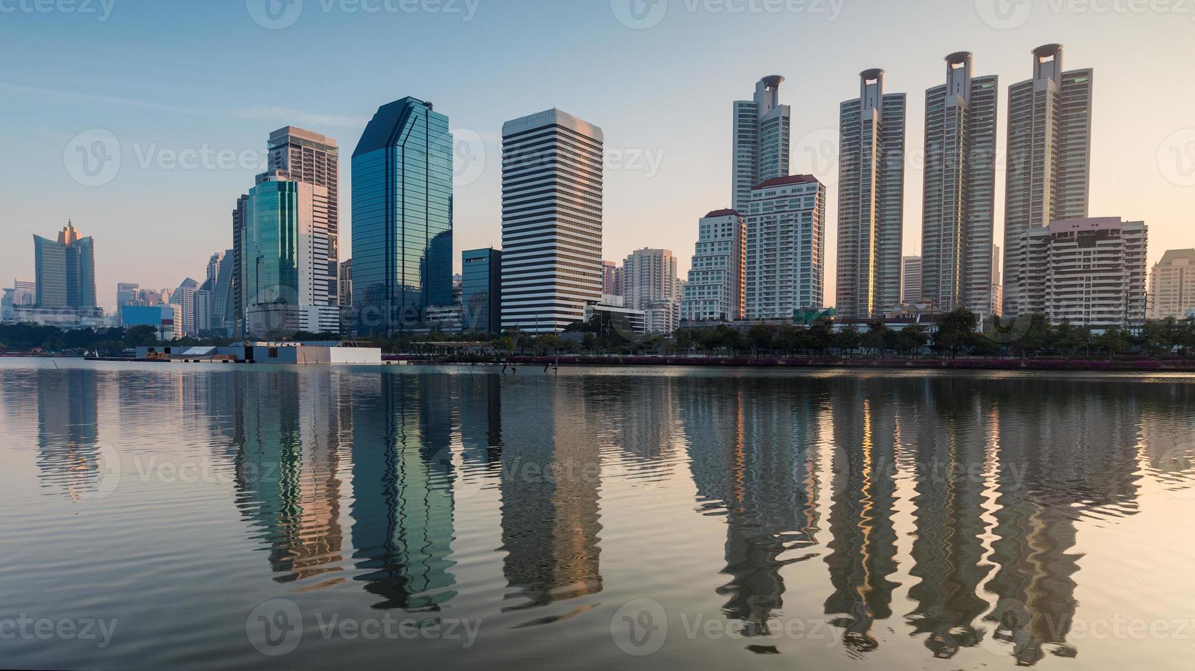Edificio de oficinas de Bangkok con reflejo de agua durante el amanecer foto