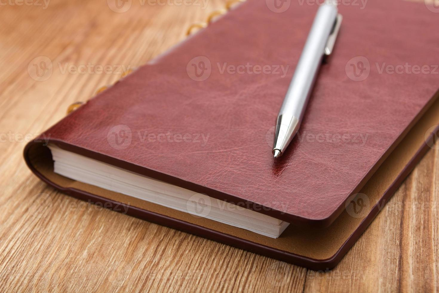 notepad with pen on wood table photo