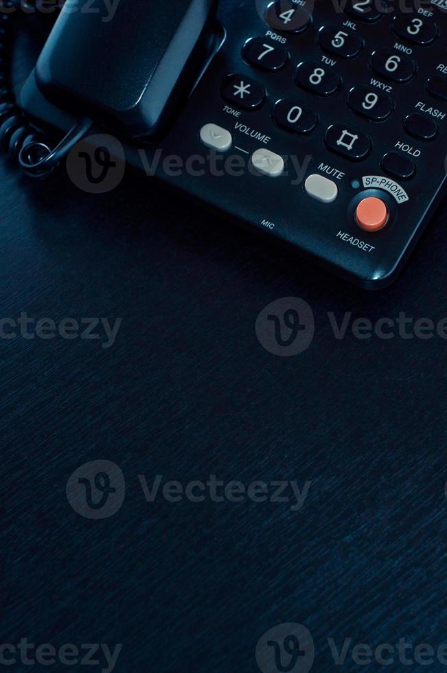 parte del teléfono en un escritorio de oficina negro foto