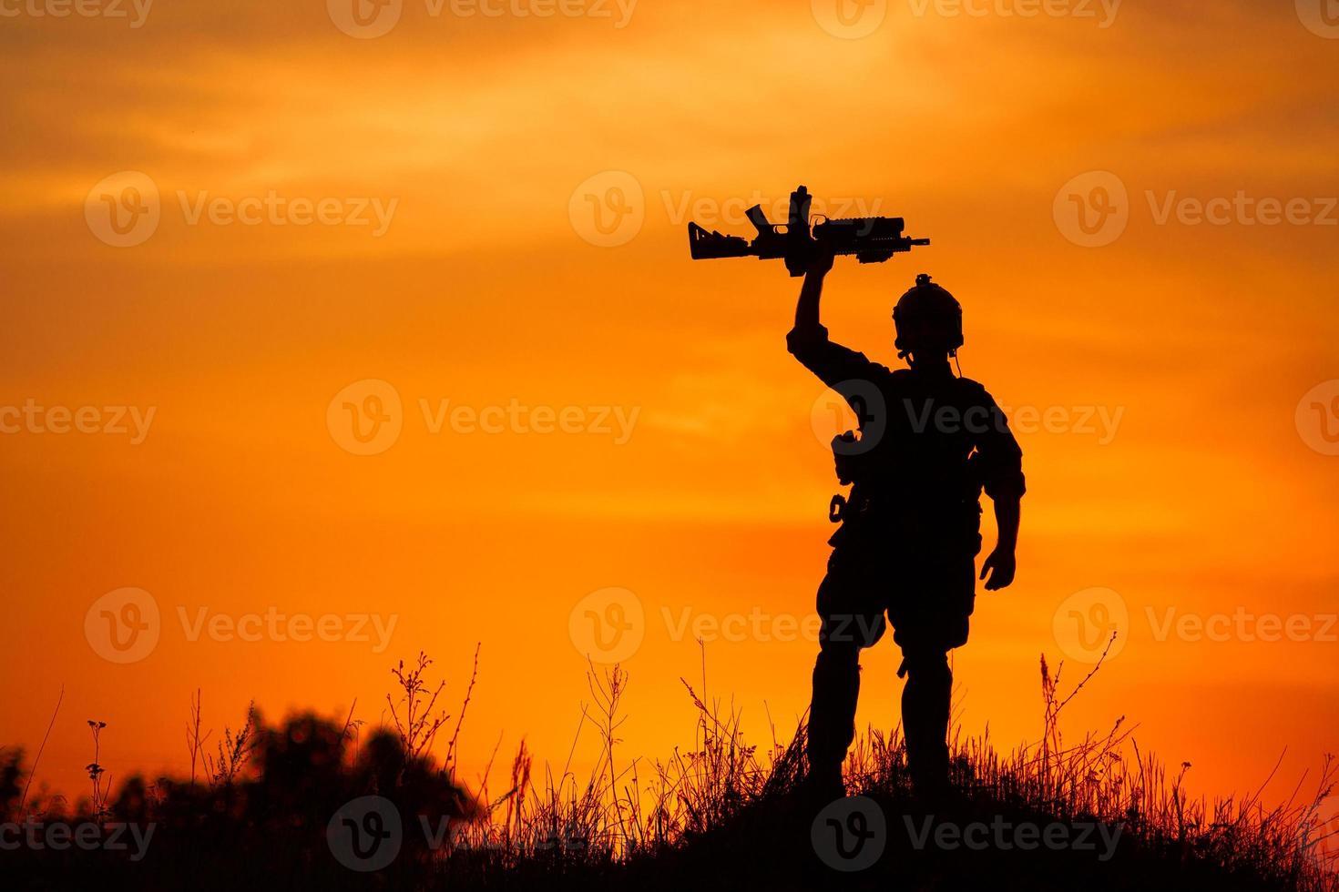 silueta de soldado militar u oficial con armas al atardecer foto