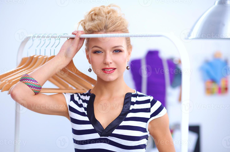 mujer hermosa joven estilista cerca de estante con perchas foto