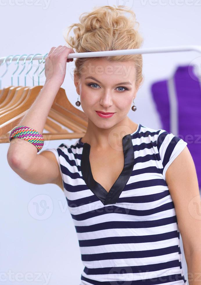 Beautiful young stylist near rack with hangers in office photo