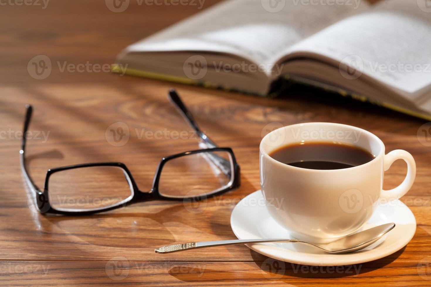 Cup of coffee, book and glasses photo