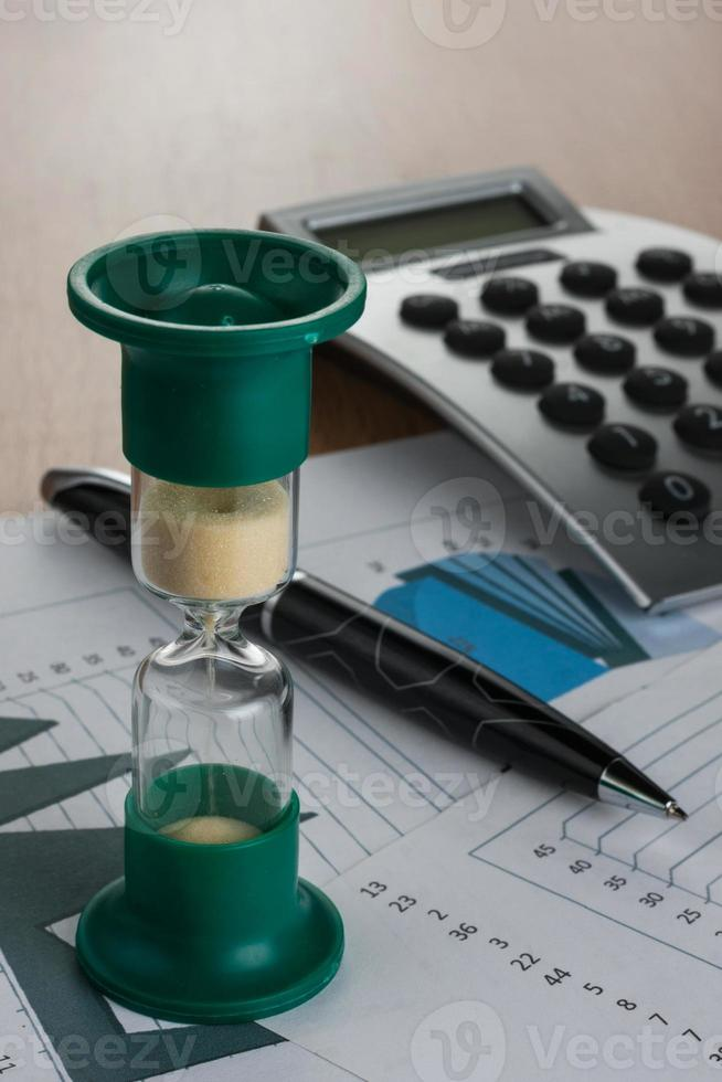 Hourglass on the table businessman photo