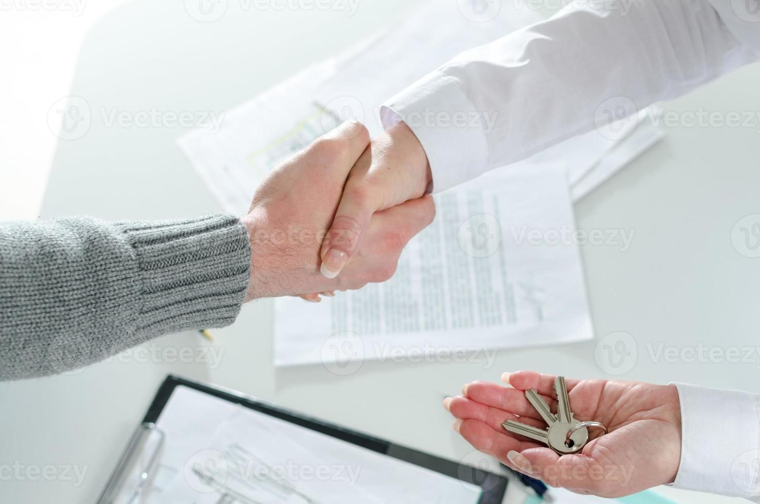 Realtor shaking hands with her client photo