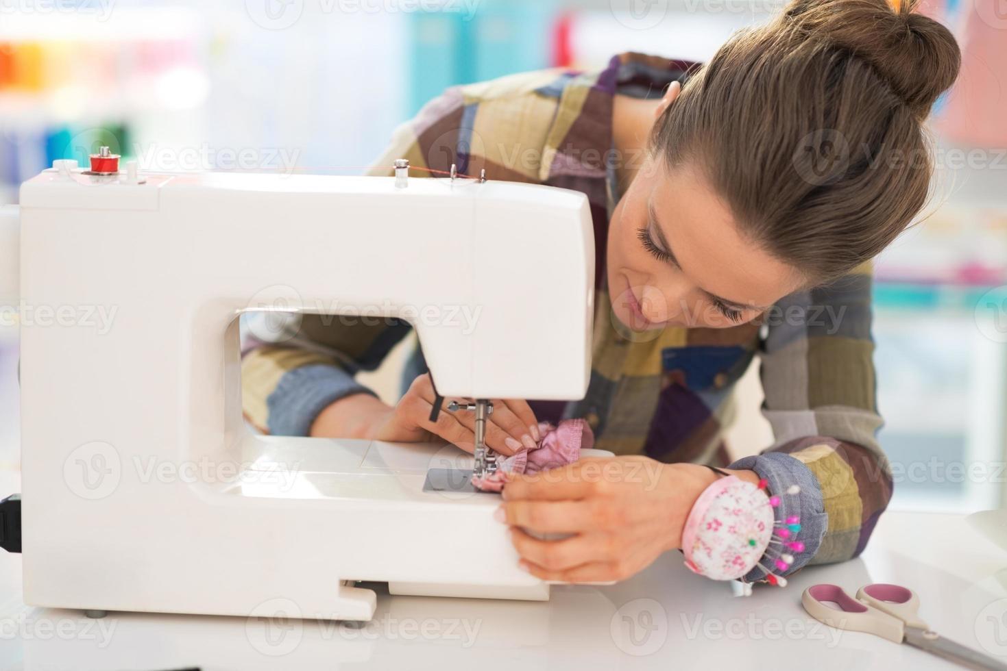 Costurera cosiendo en studio foto