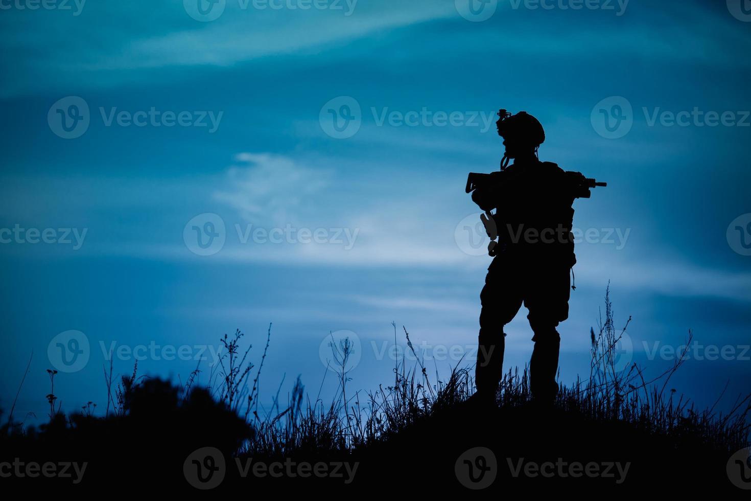 silueta de soldado militar u oficial con armas en la noche. foto