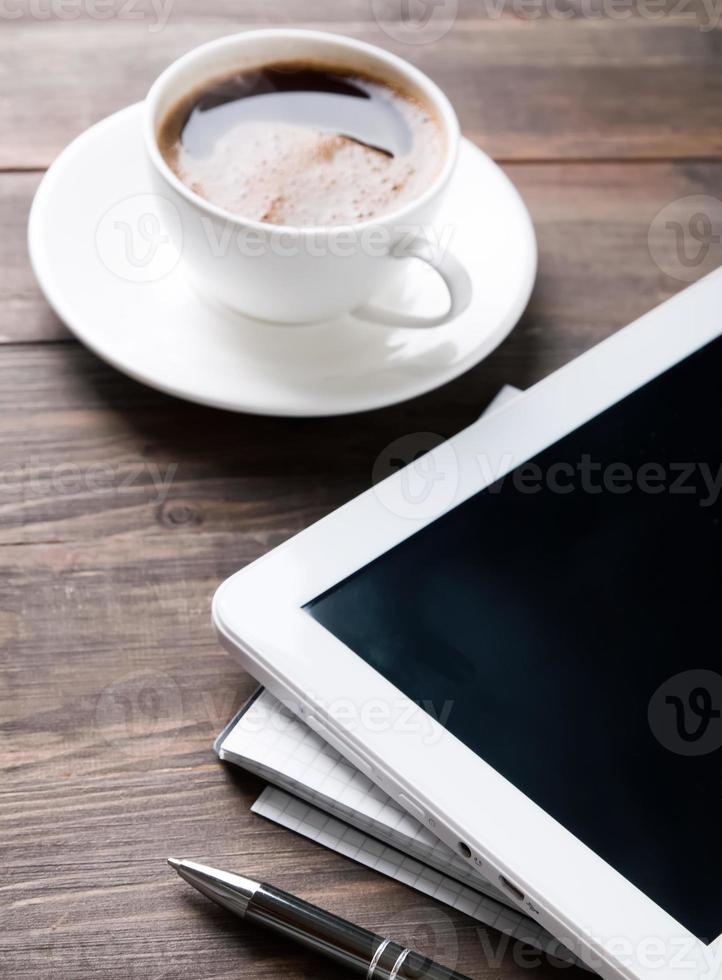 Tablet, paper notebook and coffee on the table photo