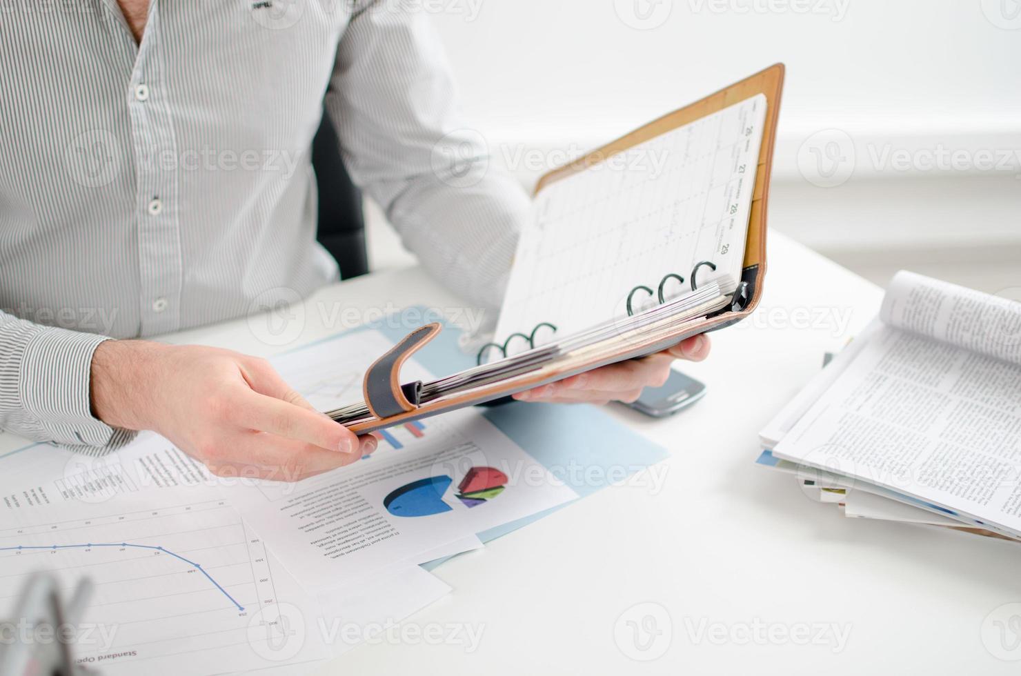 Businessman consulting his agenda photo