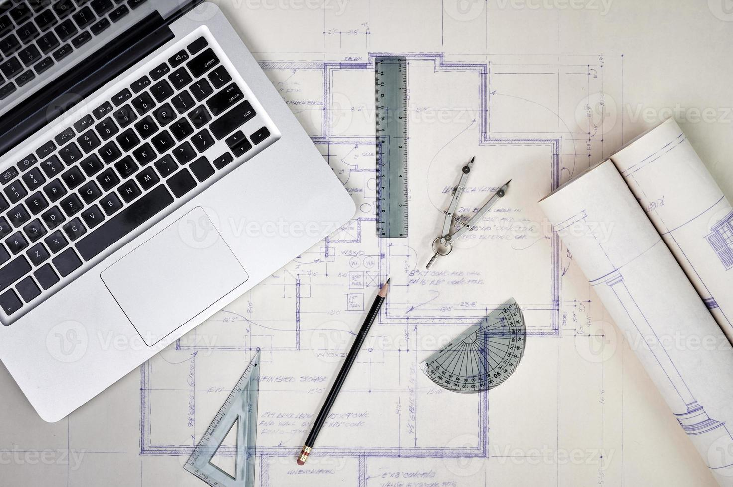 A laptop open with blueprints and architectural tools photo