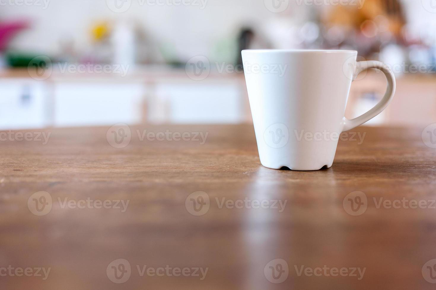 Cup of coffee with vintage kitchen defocused background. photo