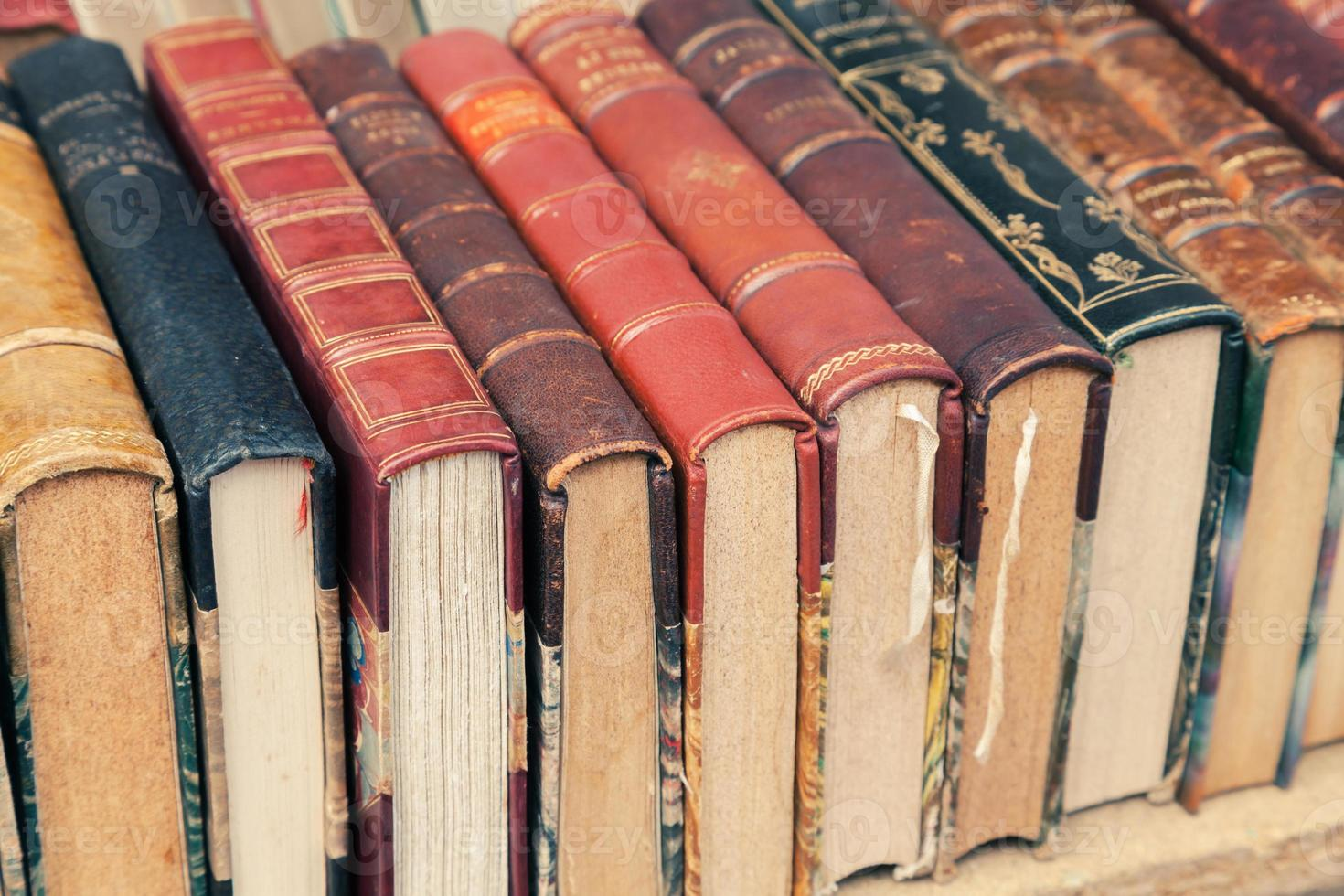 Old used vintage books lay on the shelf photo