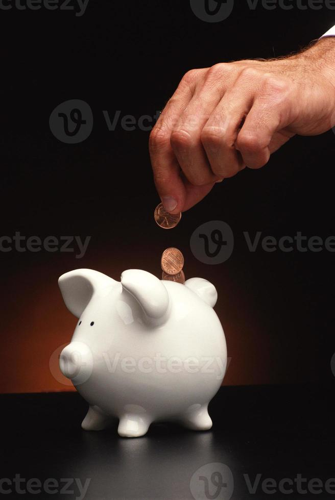 hand inserting coin into piggy bankq photo