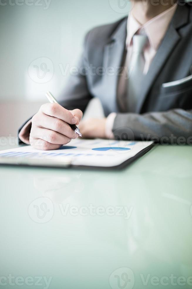 business report and man hand with pen photo