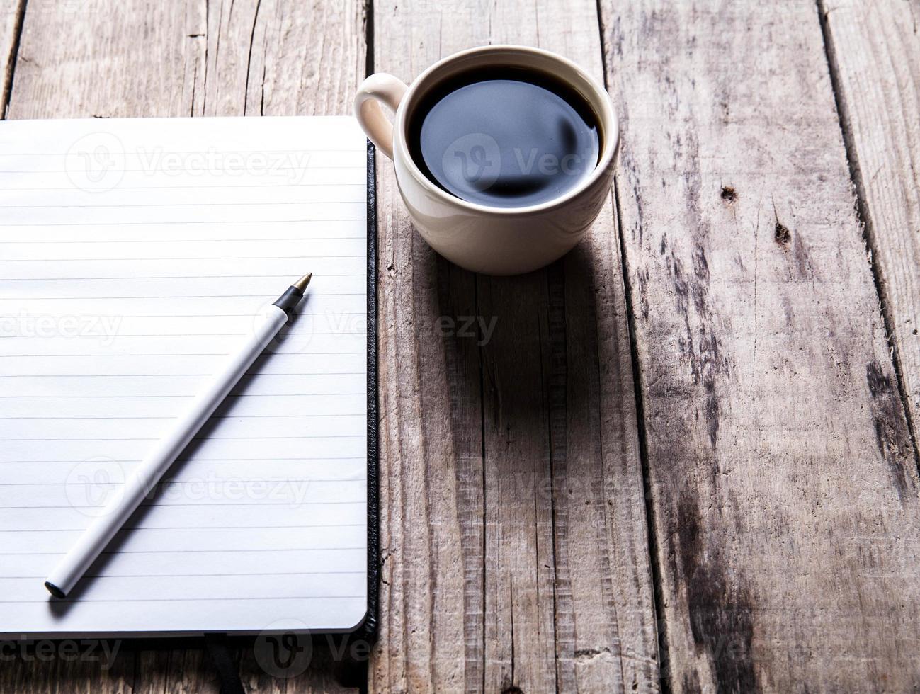 cuaderno con bolígrafo y café en la mesa de madera vieja foto
