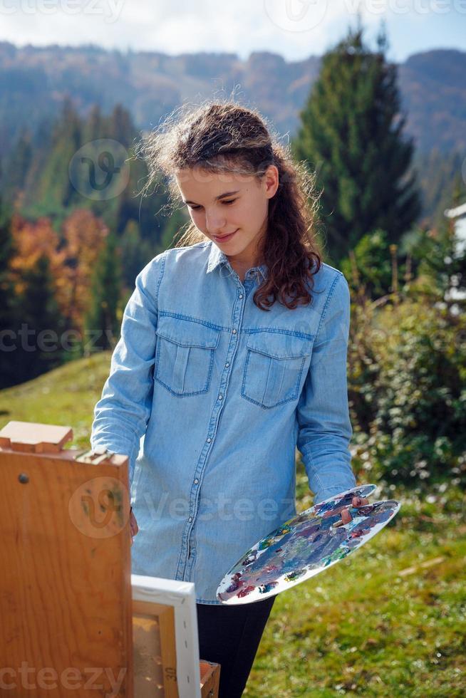 joven pintor en el trabajo en las montañas foto
