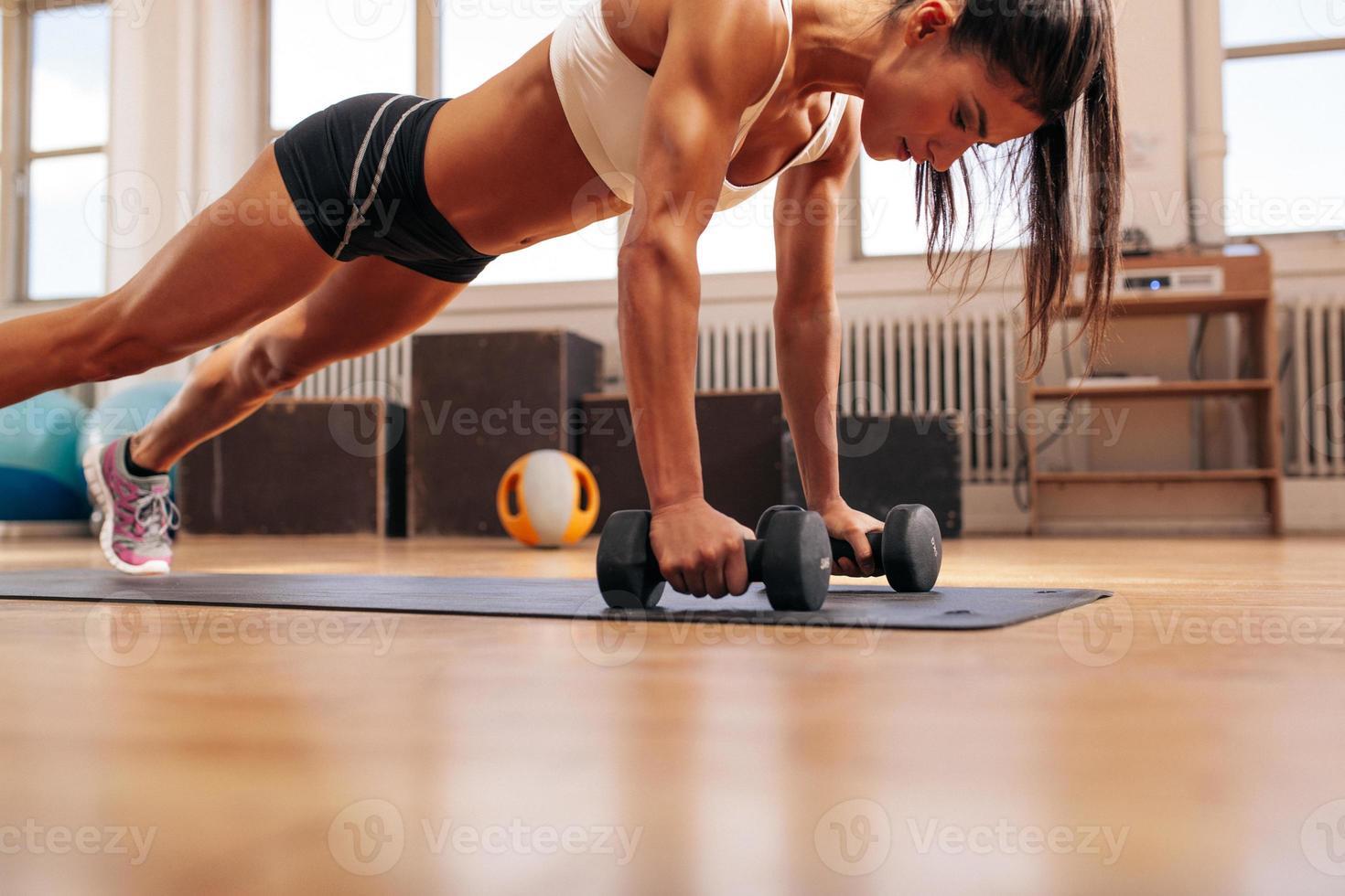 Fitness mujer haciendo flexiones ejercicio con pesas foto