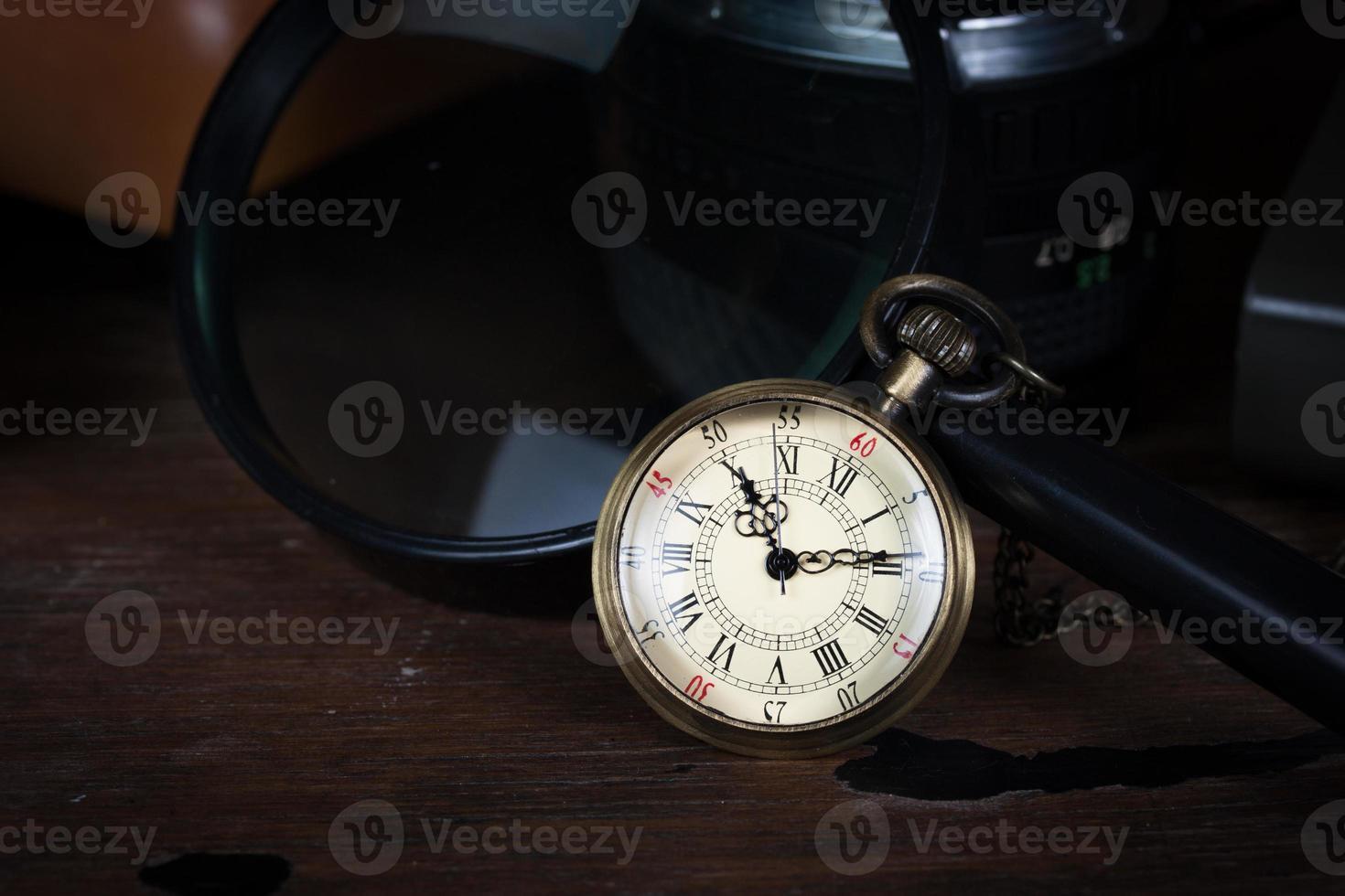 concepto de tiempo, reloj antiguo y lupa sobre mesa de madera foto