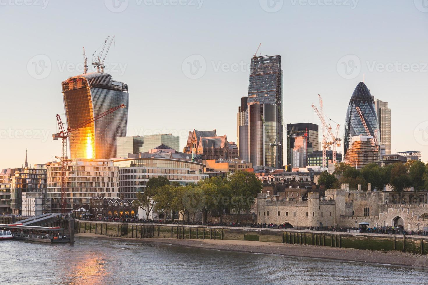 Tower of London and Modern Skyscrapers on Background at Sunset photo