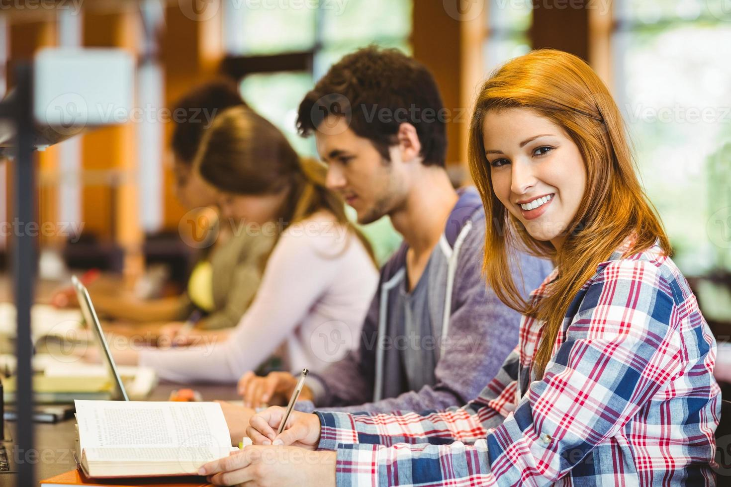 Student looking at camera while studying with classmates photo