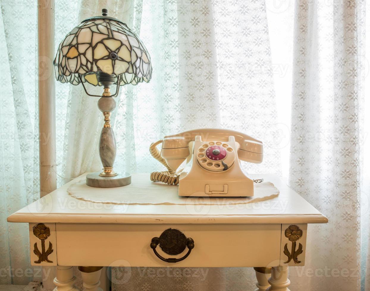 Teléfono retro con lámpara vintage en mesa de madera junto a la ventana. foto