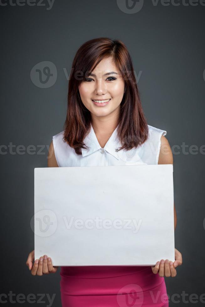 chica asiática espera signo en blanco y sonríe foto