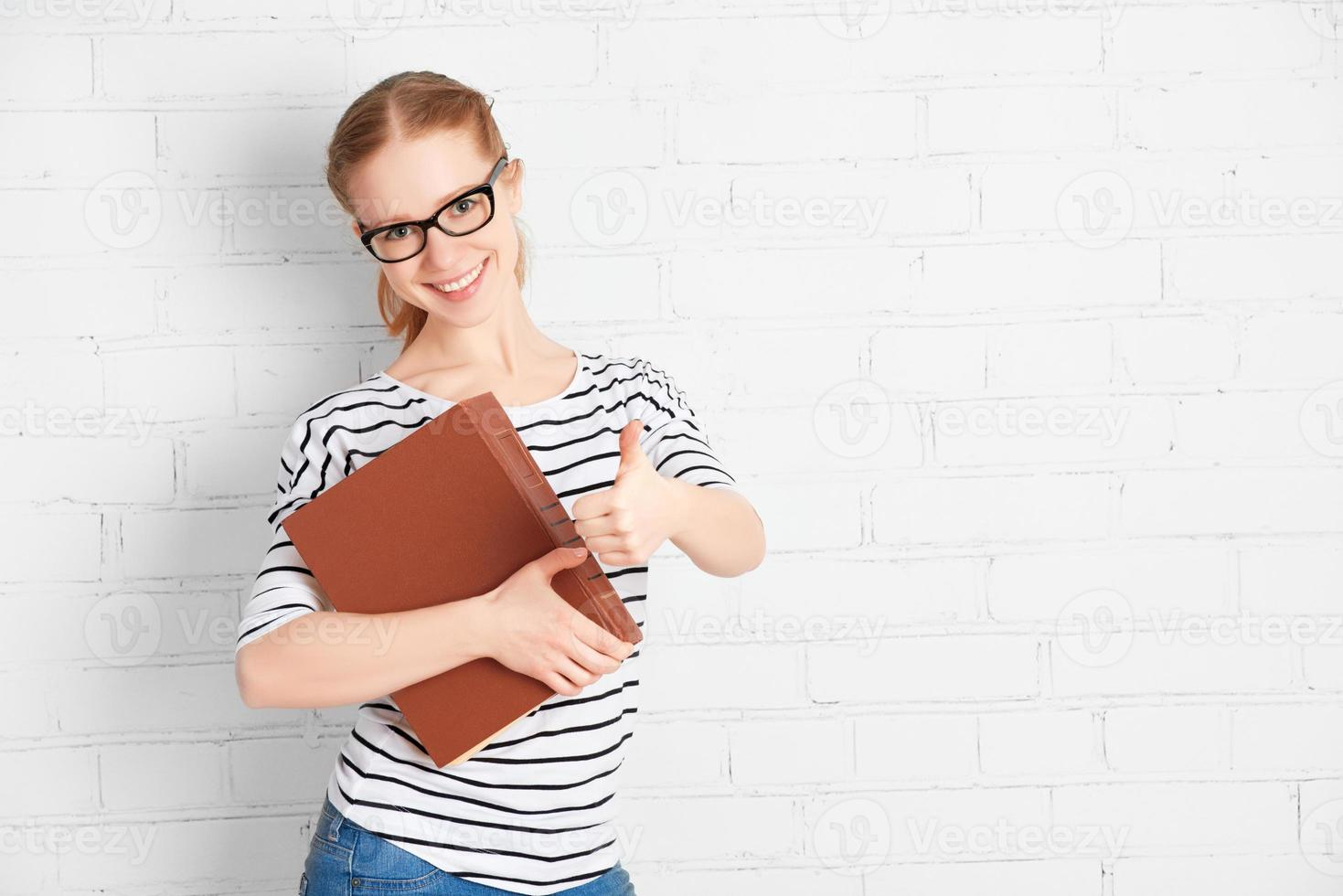 Happy successful student girl with book showing thumbs up photo