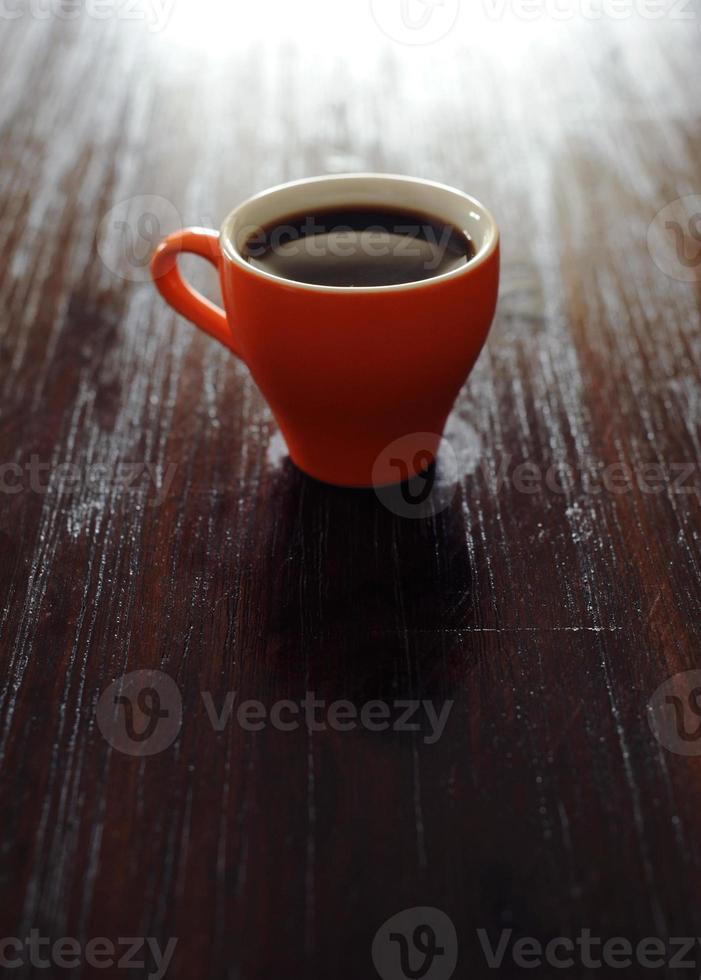 Orange mug with coffee on table, bright image photo