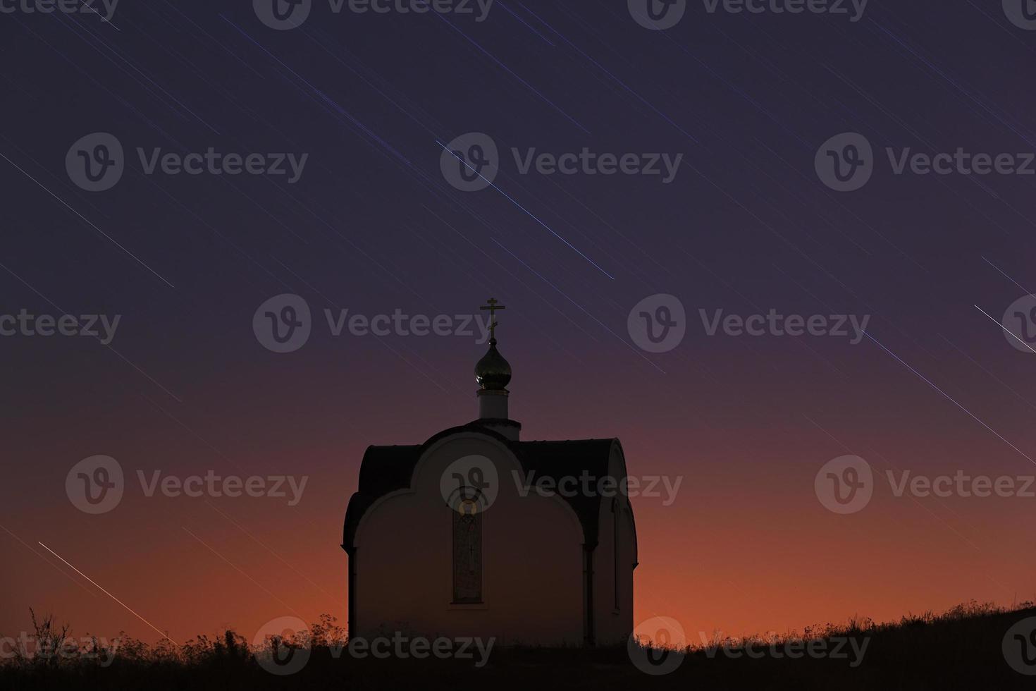 rastros de las estrellas en el cielo nocturno sobre la iglesia ortodoxa foto