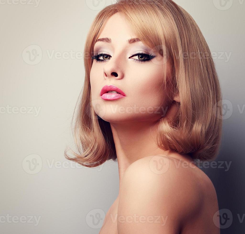 mujer hermosa maquillaje elegante con peinado corto rubio. tonificado foto