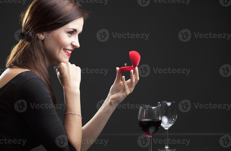 mujer con anillo de compromiso en restaurante foto