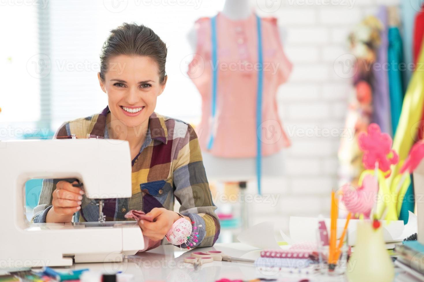Costurera feliz cosiendo en studio foto