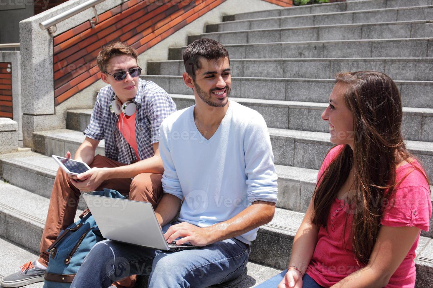 Happy students using digital tablet photo