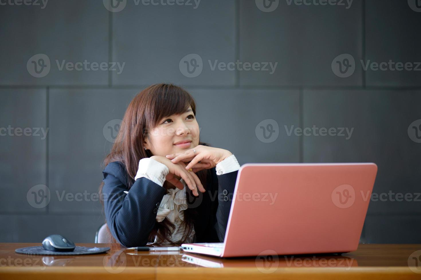 Attractive smiling young business woman using laptop at work desk photo